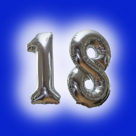 Silver number 18 party balloons isolated on a blue background  with a glow around the numbers Archivio Fotografico