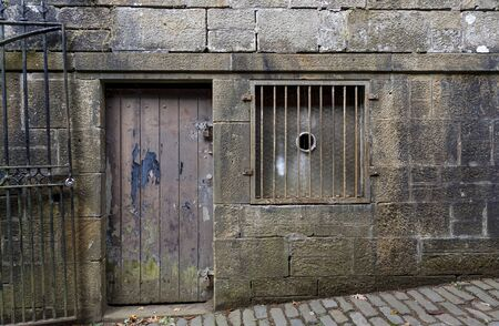Landscape image of an ancient distressed wooden door with peeling paintwork, and a stone surround, and cobbled street