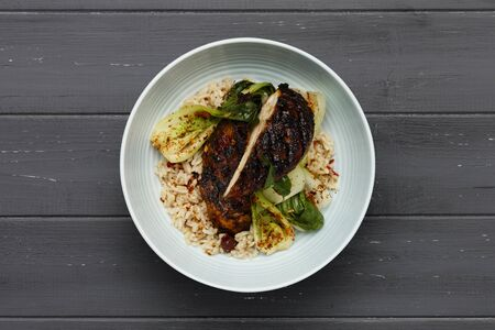 A delicious bowl of Jerk chicken, rice and vegetables, in a light blue bowl shot on a distressed dark wooden background 스톡 콘텐츠