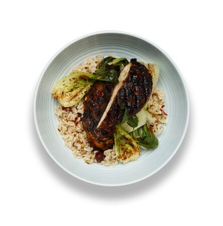 A delicious bowl of Jerk chicken, rice and vegetables, in a light blue bowl isolated on a white background