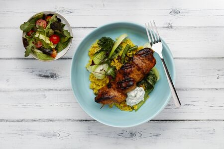 A delicious bowl of  tandoori chicken, vegetables and rice, in a light blue bowl shot on a rustic white wooden background with a  side salad