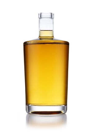 A full angular shaped bottle of golden whisky, with no label or branding, isolated on white with a slight reflection