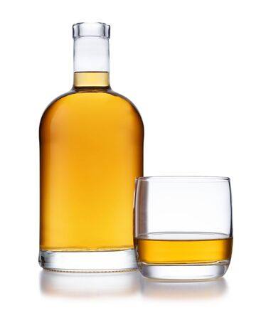 A full bell shaped bottle of golden whisky, with no label or branding, and a glass of whisky, isolated on white with a slight reflection Foto de archivo