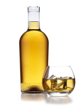 A full bottle of golden whisky, with no label or branding, and a circlular shaped glass of whisky and ice, isolated on white with a slight reflection
