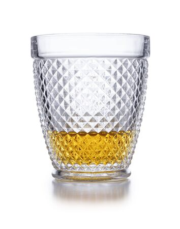 An ornate  crystal glass containing scotch whisky shot on white, with a drop shadow