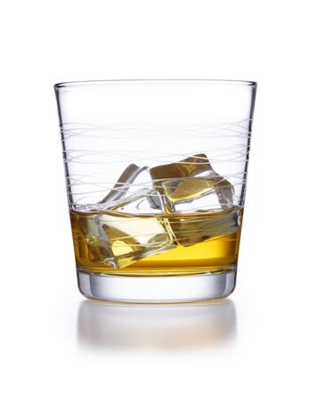 A isolated ornate tumbler style glass of whisky and ice, shot on white with a slight reflection