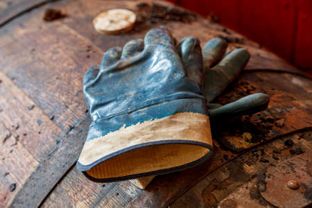 close up of a pair of gloves, on the top of a dusty old whisky barrel, in a dirty warhouse.