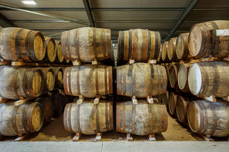 Rows of stacks of traditional full whisky barrels, set down to mature, in a large warehouse facility Reklamní fotografie