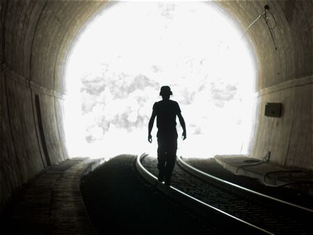 Dark shilouette of a man walks on railway bar, inside dark concrete tunnel