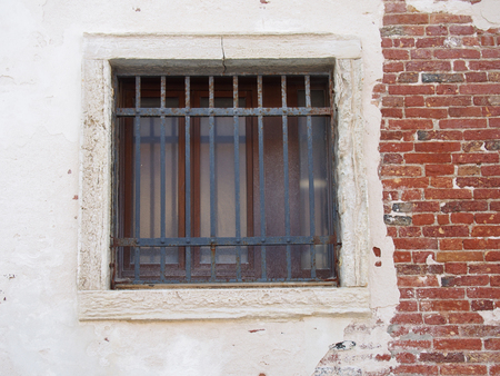 window with bars in an old distressed white and brick wall