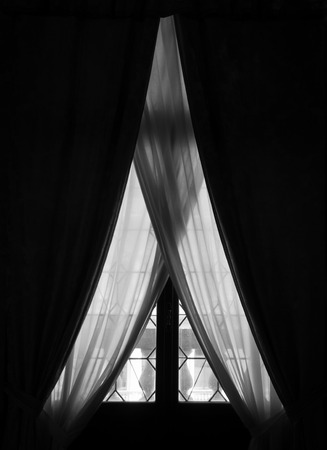 stateroom: Elegant old window with curtains and drapes in a dark room Stock Photo