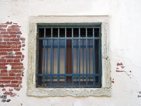 iron barred: sqaure exterior window with bars on a white wall with bricks showing though