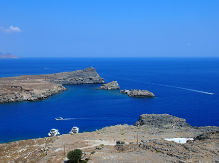 coastline and bay at lindos rhodes with islands sea boats and blue sky