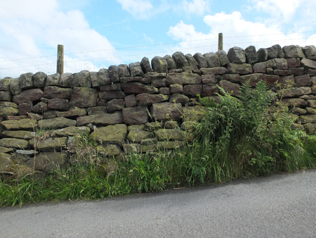 traditional dry stone wall in yorkshire on a hill with roadside and grass