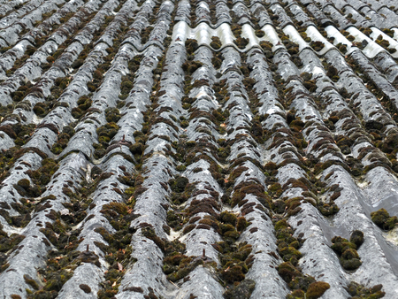 old asbestos roof tiles with moss ans repairs with vertical lines Reklamní fotografie