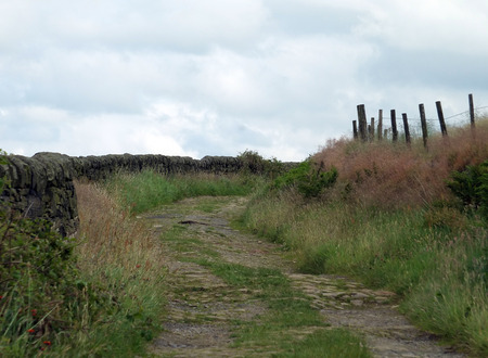 country lane and footpath winding around a hill on yorkshire pennine landscape