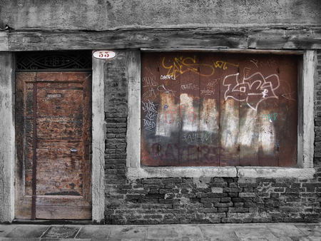 buisiness: derelict decaying shop building with boarded up window and vandalism