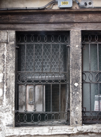metal grate: old dirty ancient window with bars and mailbox wooden frame and wire