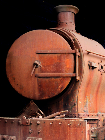 old rusting abandoned steam locomotive from the front showing door buffers and chimney on a black background