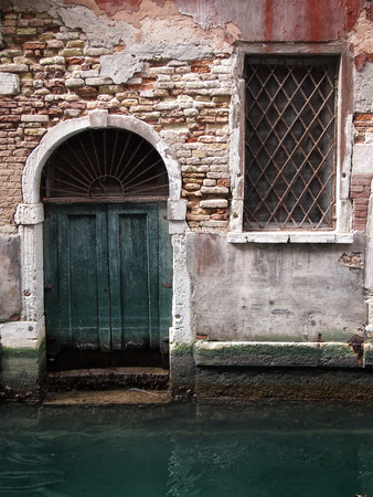 old green door in an ancient brick building with window and arched doorway on a canal in venice with reflection in the water damp walls and crumbling painted plaster
