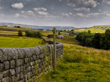 visible: Fields with  traditional dry stone wall and wooden sign in yorkshire pennine countryside with trees farms and mountains visible Stock Photo