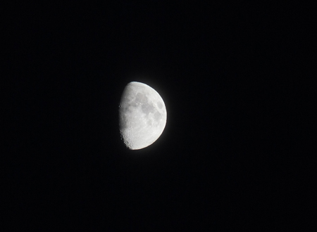 two and two thirds: silver two thirds bright moon in a black sky showing seas and craters in shadow