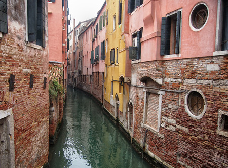 small canal in venice with old buildings balconies a fading painted walls Stock Photo