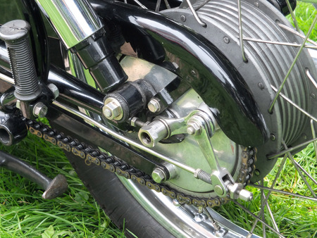 shocks: rear wheel of a black vintage motorcycle with tyre, chain and brake drum