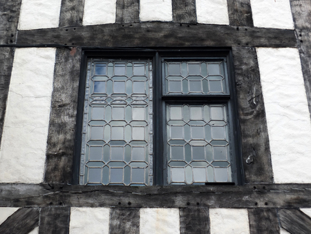 shakespearean: leaded glass window in a half timbered medieval type building with black oak beams and white plaster walls Stock Photo
