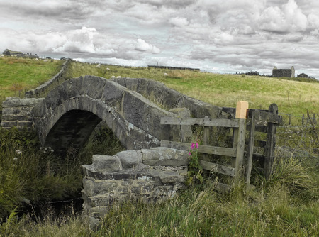 an ancient stone medieval packhorse bridge in colden near hebden bridge in west yorkshire in pennine moorland landscape with grazing sheep an ruined farm building in the background