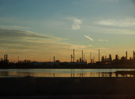 industrial landscape on the coast with pipes towers and refinery chimneys from manufacturing with reflections of buildings in the sea at sunset