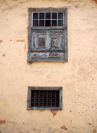 two old wooden windows with ancient faded peeling green paint metal bars shutters and panels on an old plastered peeling concrete terracotta and beige wall with stains and cracks 版權商用圖片