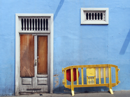 derelict abandoned boarded up blue house with white broken door bars ans plastic yellow barrier in the street 版權商用圖片
