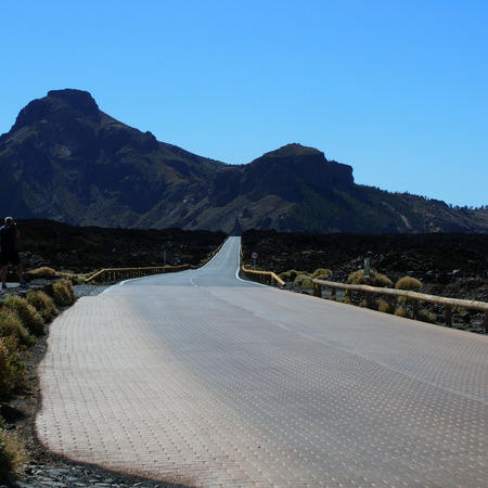 curve: empty winding curced road with distant mountains and blue sky in teide national park in tenerife
