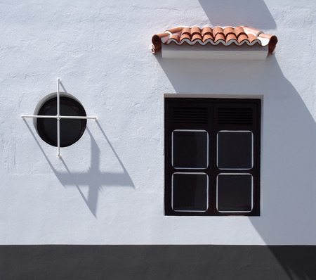 white painted building with round and square window with shutters and tiled detail in bright sunlight with shadows