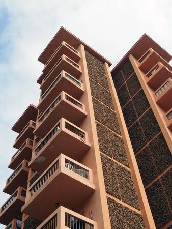 concrete apartment blocks with orange balconies and details vertical view with blue sky