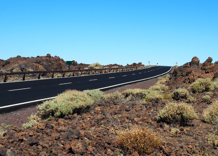 empty two lane blacktop road in the desert with scrub plants arid landscape and blue sky Stock Photo