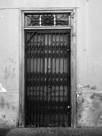 old doors with black iron security gate on a shabby distressed wall with exposed concrete Stock Photo