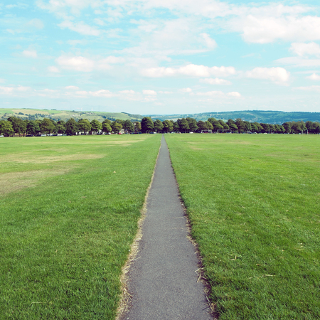 long straight footpath stratching to the distance in a park with grass lawn and trees in the background in halifax yorkshire