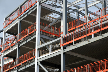 construction site of steel framed development with orange safety fencing