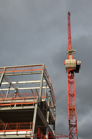 construction site with metal framework and tall orange crane