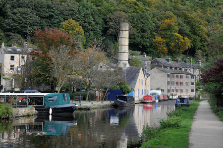 canal and marina in hebden bridge with barges houseboats and old mill buildings surrounded by trees