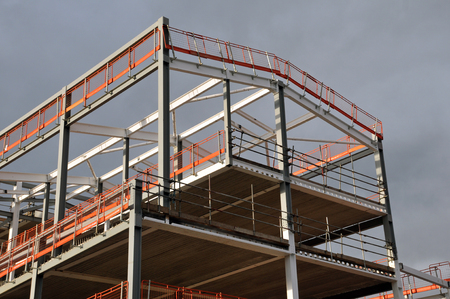 steel frame and roof of a building under construction with orange safety railings and gray girders