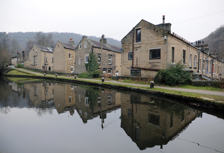 Streets of terraced houses alongside the rochdale canal in hebden bridge with reflections in the water in winter
