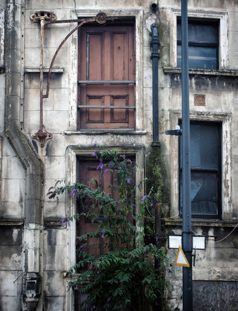facade of a derelict collapsing abandoned commercial property in a city center