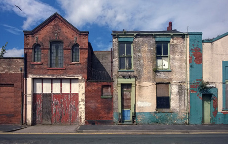 derelict houses and abandoned commercial property on a residential street with boarded up windows and decaying crumbling walls