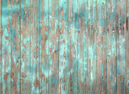 flaking blue painted old grey wooden plank wall or fence Stock Photo