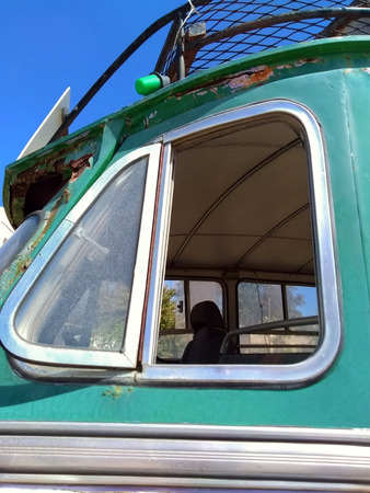 close up of the side window of an old green rusty vintage bus
