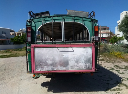 rear view of an old rusting green painted bus with roof rack parked in a rustic location in cyprus