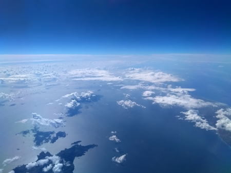 aerial view of bright blue sea and sky with white clouds casting shadows Stock Photo